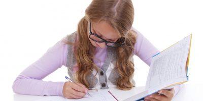 Likinäköinen tyttö tekemässä läksyjä